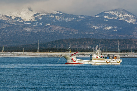 kuril: fishing boat on background of winter mountains Stock Photo