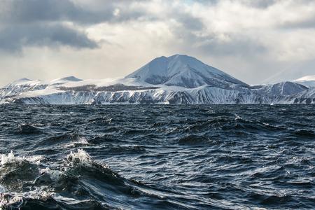 far east: volcán en el invierno en la isla en las nubes