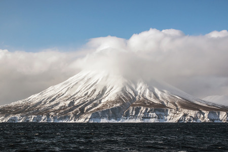 tectonics: volcano in the winter on the island in the clouds Stock Photo