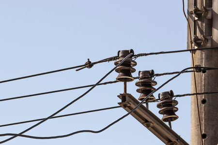 electric current: ceramic insulators electric current with wires on a background blue sky