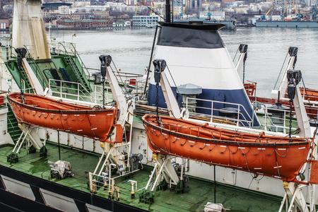 lifeboats: two orange lifeboats on the ships davits Stock Photo