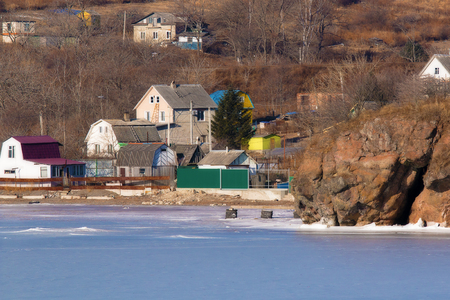 houses on the shore of the frozen sea in the snowless winter Foto de archivo - 96488107