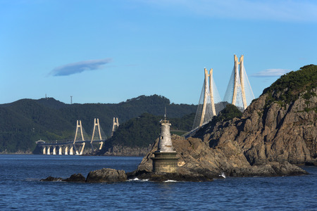 cable-stayed bridge to the island with a lighthouse on the rocks