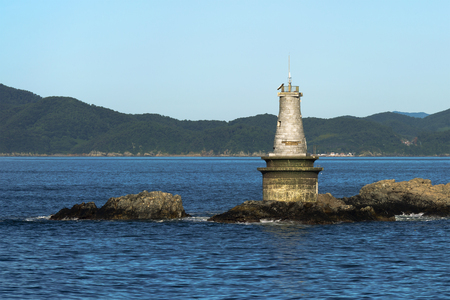 reefs in the sea with a lighthouse on the rocks Foto de archivo