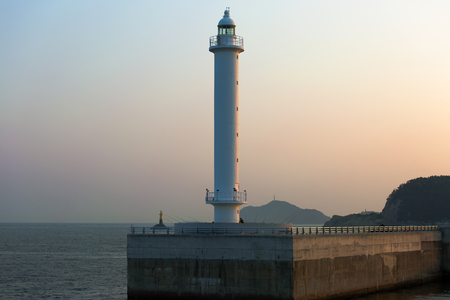 lighthouse at the exit of the port illuminated by the sunset Foto de archivo