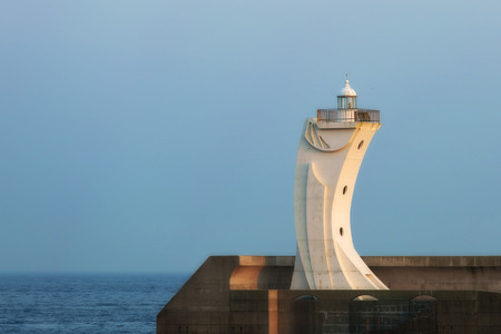white lighthouse on the pier of the South Korean city of Busan during sunset Foto de archivo