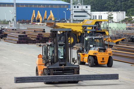 transportation of steel blanks on the pier by forklifts Foto de archivo