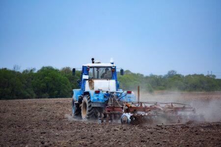 Traktor pflügt das Feld mit einem Pflug