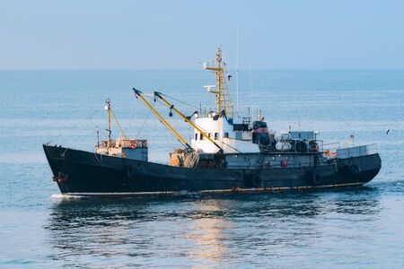 fishing trawler returns to port in the calm
