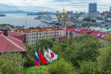 Vladivostok, Primorsky Krai, Russia, 06/09/2019, the cruise liner Costa Serena during the Eastern economic forum stands at the pier on the background of flags, the Cathedral and the Golden horn Bay Editorial