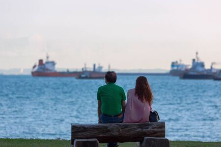 a man and a woman sit on the beach and look at the ships