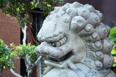 stone lion statue in traditional style at the entrance of a Buddhist temple