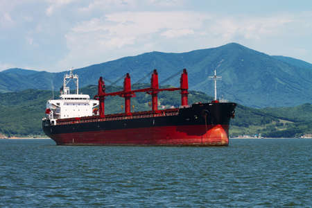 cargo ship bulker red on the background of mountains
