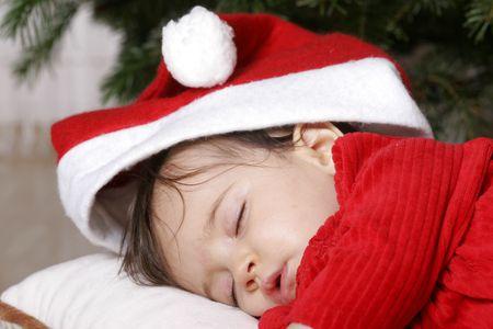 baby kerst: schattige baby met santa hoed slapen onder kerstboom