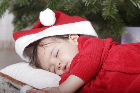cute baby with santa hat sleeping under christmas tree photo