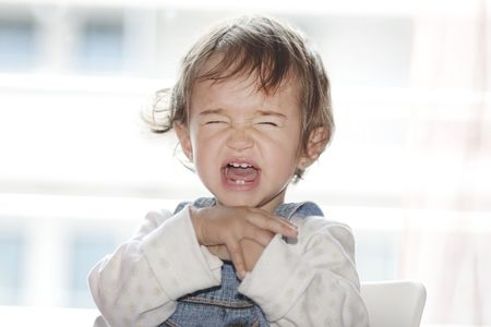 tantrum: portrait of little girl  sitting and screaming  Stock Photo