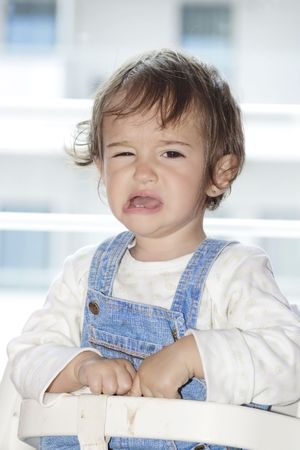 to implore: little girl sitting in her chair and crying Stock Photo