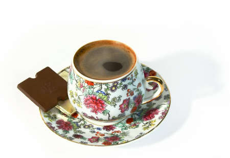 Porcelain coffee cup and two small chocs on saucer photo