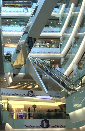 The interior of a large store with escalators, some unrecognizable buyers