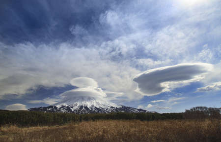 lenticular cloud: Volcano in cap rare lentitsular clouds in the cedar stlannikak, spring, Kronotsky, Kamchatka, Russia Stock Photo