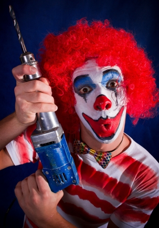 evil clown: Crazy clown, a bright make-up, a drill Stock Photo