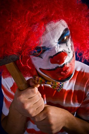 Crazy clown, a bright make-up, a hammer photo