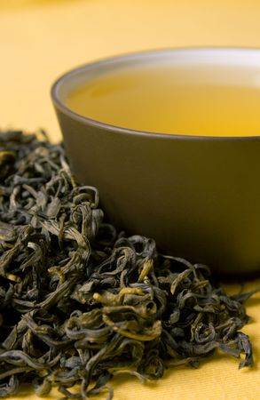 clay cup with green tea in dried tea leaves Stock Photo - 6575657