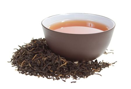 dried herb: clay cup with black tea in dried tea leaves on a white background