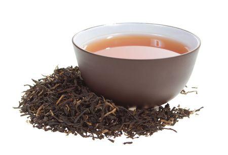 hojas de te: taza de arcilla con t� negro en seco de t� deja sobre un fondo blanco