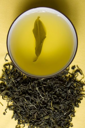 tea tree: clay cup with green tea and tea leaves in dried tea leaves