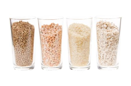 oatmeal, buckwheat, rice and peas in a four transparent glass on a white background photo