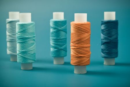 Upright colored spools of thread on a blue background photo