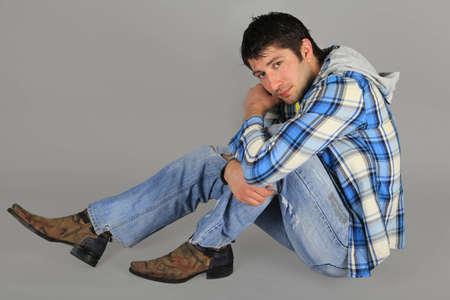 Hombre en jeans y una camisa plaid sentada en el suelo