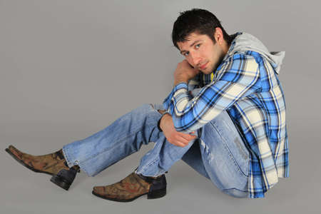 Man in jeans and a plaid shirt sitting on the floor     photo