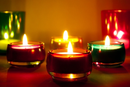 sconces: Burning candles in colored glass sconces Stock Photo