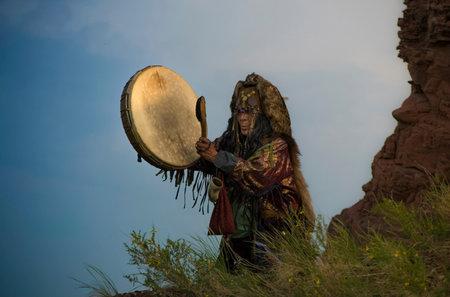 The shaman hits the tambourine on the edge of the cliff. Folk rituals. Foto de archivo