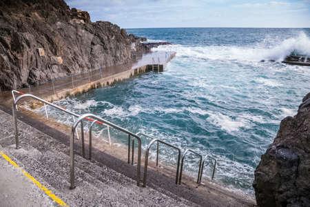 Stone pavement with railings descent to the sea. Foto de archivo