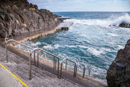 Stone pavement with railings descent to the sea. Stock Photo