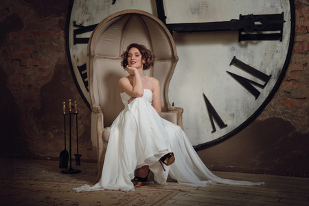 A smiling attractive girl in a wedding dress in strange chair  The bride in a chair on the background of clocks and fireplace tool set  Horizontal