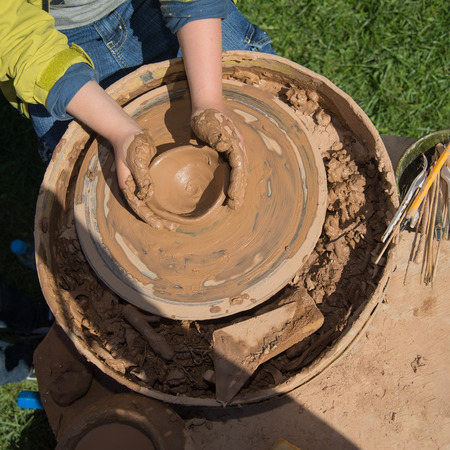 slavs: Children outdoor studying pottery using pottery wheel Stock Photo