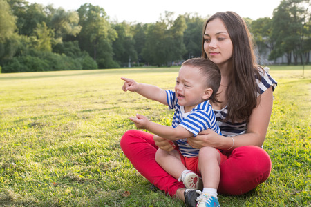 mother and child playing at the grass  naughty boy crying and and point by his finger  copy space left