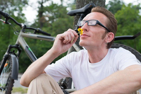 Cyclist with funny face sniffing the flower photo