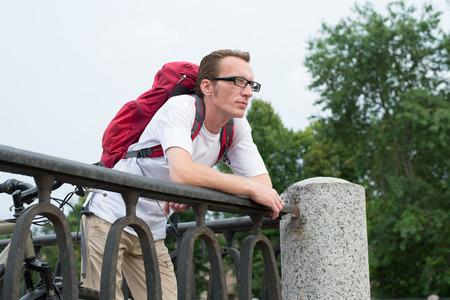 parapet: Backpacker lean on the granite embankment parapet Stock Photo