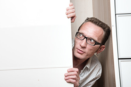 unexpectedness: Surprised man inside white wardrobe  Copy space left