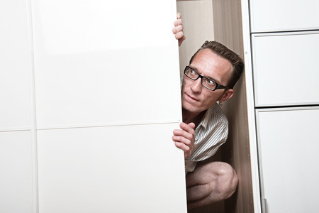 unexpectedness: Concerned man look out white wardrobe  Copy space left