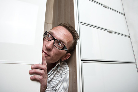 unexpectedness: Waiting revelations man look out white wardrobe  Copy space right Stock Photo