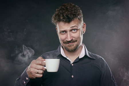 smug: handsome beard man stand in fog with cup of coffee  Stock Photo