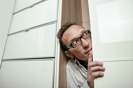 peep out: Frightened man peep out white wardrobe  Copy space right