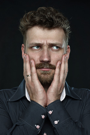 quandary: worried married handsome bearded man anxiously press his palm to face  close up portrait on dark background  Studio shot