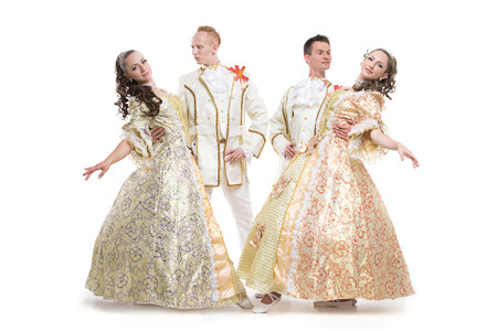minuet: Four young people, two girls and two boys, dressed in historical aristocrat costumes XVIII century posing in dance figures isolated on white background